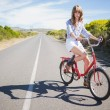 Pretty young model riding bike — Stock Photo
