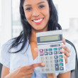 Amused businesswoman holding a calculator — Stock Photo