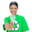Smiling model wearing recycling tshirt holding light bulb — Stock Photo