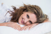 Smiling woman lying on cosy bed — Stock Photo