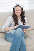 Smiling casual woman on cosy couch using tablet pc — Stock Photo