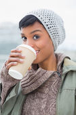 Pleased young model in winter clothes enjoying coffee — Stock Photo