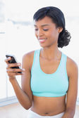 Pleased fit woman texting with her mobile phone — Stock Photo
