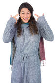Smiling curly haired model with winter clothes pointing out her head — Stock Photo