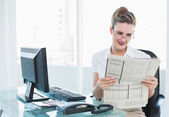 Smiling businesswoman wearing glasses reading newspaper — Stock Photo