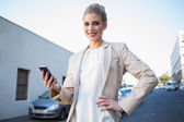 Cheerful elegant businesswoman holding smartphone — Stock Photo