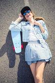 Smiling blonde skater lying on the highway — Stock Photo