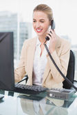 Smiling pretty businesswoman answering the phone — Stock Photo