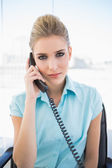 Serious stylish businesswoman answering the phone — Stock Photo