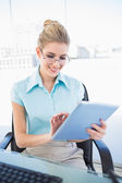 Cheerful businesswoman wearing glasses using tablet — Stock Photo