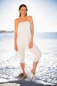 Жизнерадостная женщина на пляже с босиком в море — Стоковое фото
