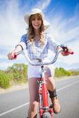 Smiling trendy woman posing while riding bike — Stock Photo