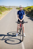 Femme souriante avec le vélo sur route — Photo