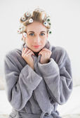 Lovely relaxed blonde woman in hair curlers looking at camera — Stock Photo