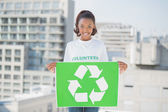 Cheerful woman holding recycling sign — Stock Photo