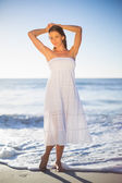 Beautiful woman in white summer dress posing — ストック写真
