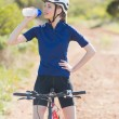 Woman with bike drinking water — Stock Photo