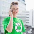 Cheerful woman wearing recycling tshirt having a call — Stock Photo