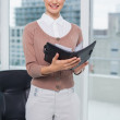 Smiling businesswoman holding notebook — Stock Photo