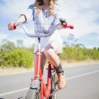 Thoughtful young woman posing while riding bike — Stock Photo