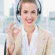 Smiling pretty call centre agent giving okay gesture — Stock Photo