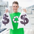 Smiling woman in green recyling tshirt showing money bags — Stock Photo