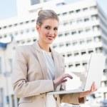 Happy gorgeous businesswoman working on laptop — Stock Photo