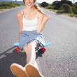 Cool skater girl doing sitting on her skateboard — Stock Photo