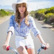 Mysterious young woman posing while riding bike — Stock Photo