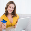 Smiling woman holding laptop showing credit card — Stock Photo #31567061