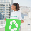 Cute volunteer woman holding recycling sign looking away — Stock Photo