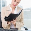 Focused attractive businesswoman writing on her agenda — Stock Photo