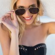 Smiling blonde in elegant black bikini looking over her sunglass — Stock Photo #31568599