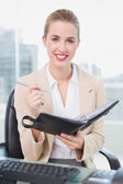 Smiling attractive businesswoman writing on her agenda — Stock Photo