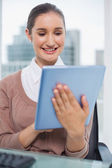 Happy beautiful businesswoman scrolling on her tablet — Stock Photo