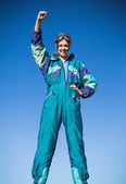 Smiling woman in ski suit putting hand up — Stock Photo