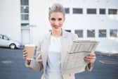 Smiling stylish businesswoman holding newspaper and coffee — Stock Photo