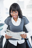 Happy businesswoman holding newspaper — Stock Photo