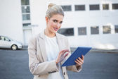 Cheerful stylish businesswoman scrolling on digital tablet — Stock Photo