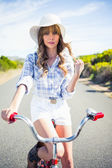 Trendy young woman posing while riding bike — Stock Photo