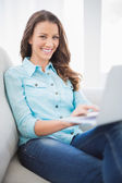 Cheerful gorgeous brunette sitting on sofa using laptop — Stockfoto