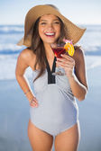Happy woman in swimsuit wearing straw hat holding cocktail — Stock Photo