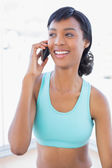 Laughing fit woman calling someone with her mobile phone — Stock Photo