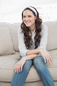 Casual pretty woman sitting on a cosy couch — Stock Photo