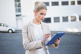 Serious stylish businesswoman scrolling on digital tablet — Stock Photo