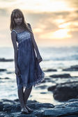 Beautiful model standing on rocks by the sea — Stock Photo