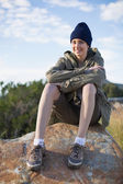Smiling woman wearing cap sitting on a rock — Stock Photo