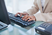 Close up on businesswoman typing on her keyboard — Stock Photo