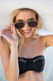 Smiling blonde in elegant black bikini looking over her sunglass — Stock Photo