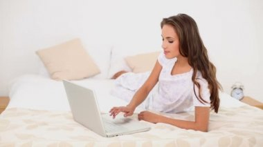 Young woman using her laptop lying on her bed — ストックビデオ